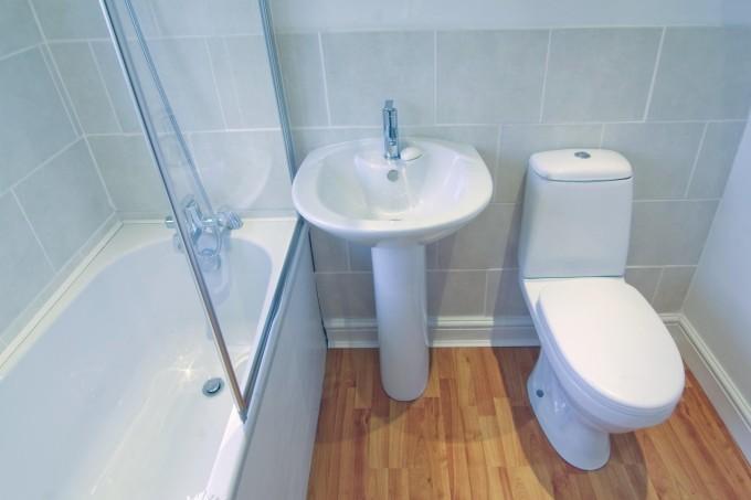 Плитка холодных тонов делает туалет визуально шире
