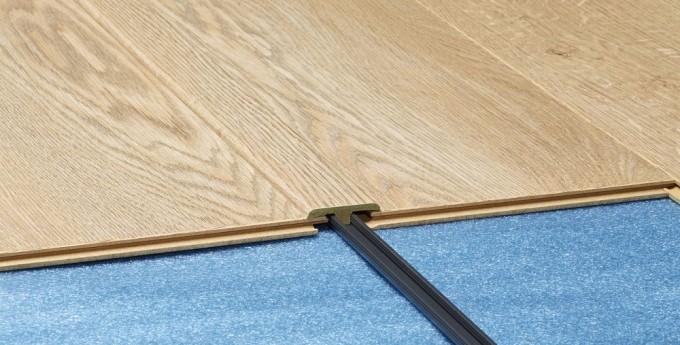 Пороги используют для того, чтобы скрыть швы между напольными покрытиями